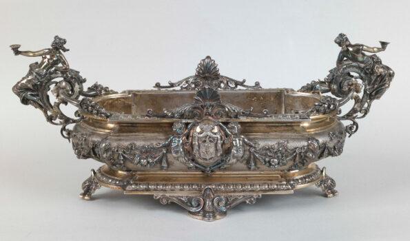 Centro tavola in argento sbalzato e cesellato con figure femminili e putti al centro lo stemma della famiglia Torlonia