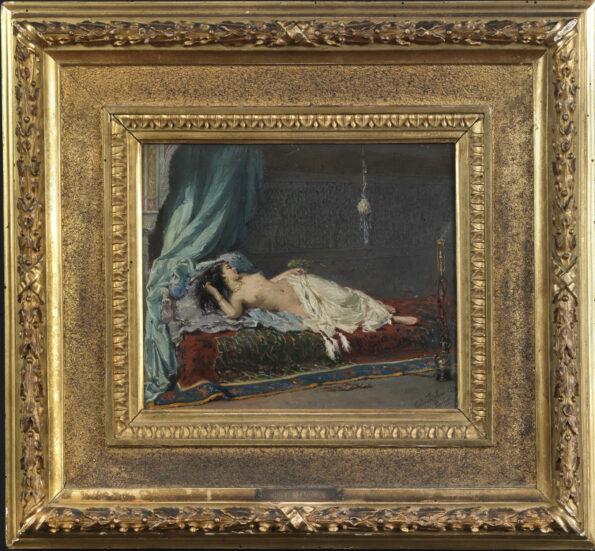 Olio su tela entro cornice intagliata e dorata raffigurante scena d'interno con odalisca adagiata su un letto che gioca con un pappagallo