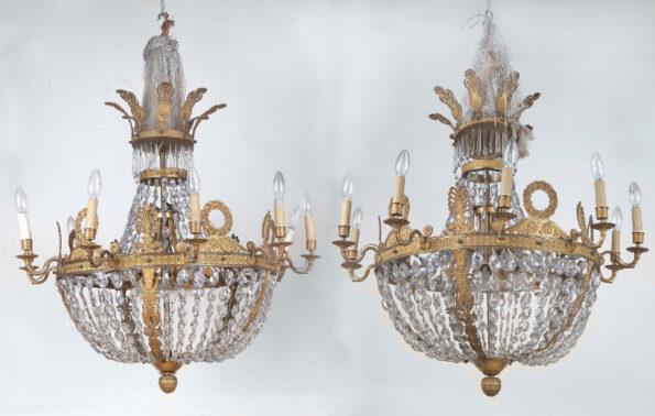 Coppia di lampadari in bronzo dorato e cristallo, cesellati a motivi vegetali e a motivi classici del periodo dell'impero